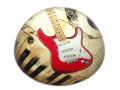 Glass domed paperweight featuring an image of a red electric guitar, a section of a keyboard, part of a treble clef and some music notes.
